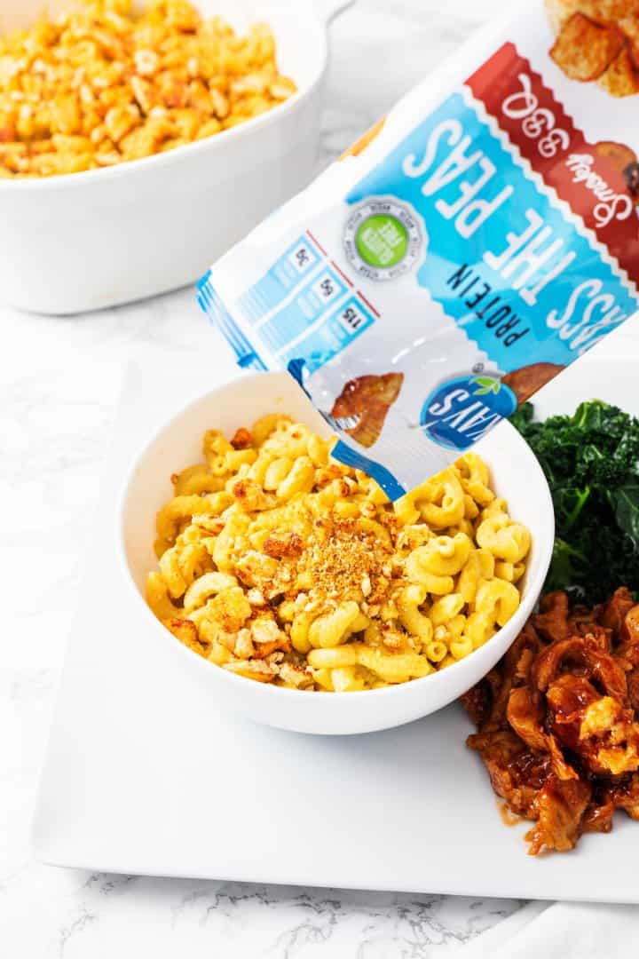 Bowl of vegan mac n cheese in plate with kale, seitan, and barbecue sauce with bag of bbq chips pouring in bowl