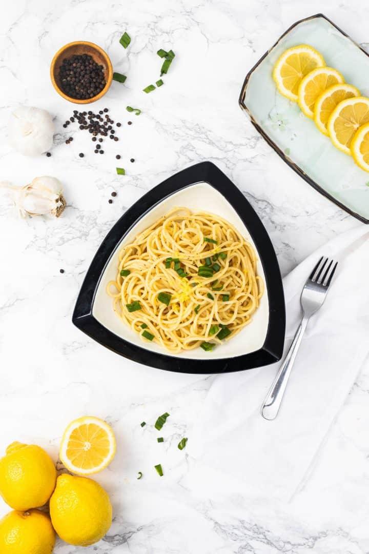 Bowl of lemon pepper pasta with sliced lemons, garlic, and pepper on the side