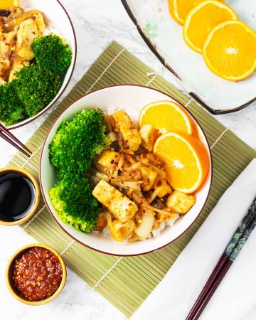 Bowls of orange tofu with broccoli on table setting with chopsticks