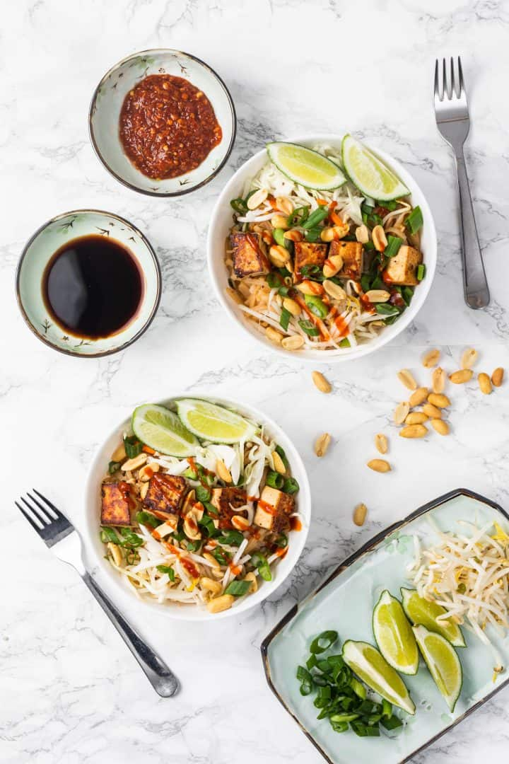 Bowls of pad thai with garnishes and sauces on plates to the side