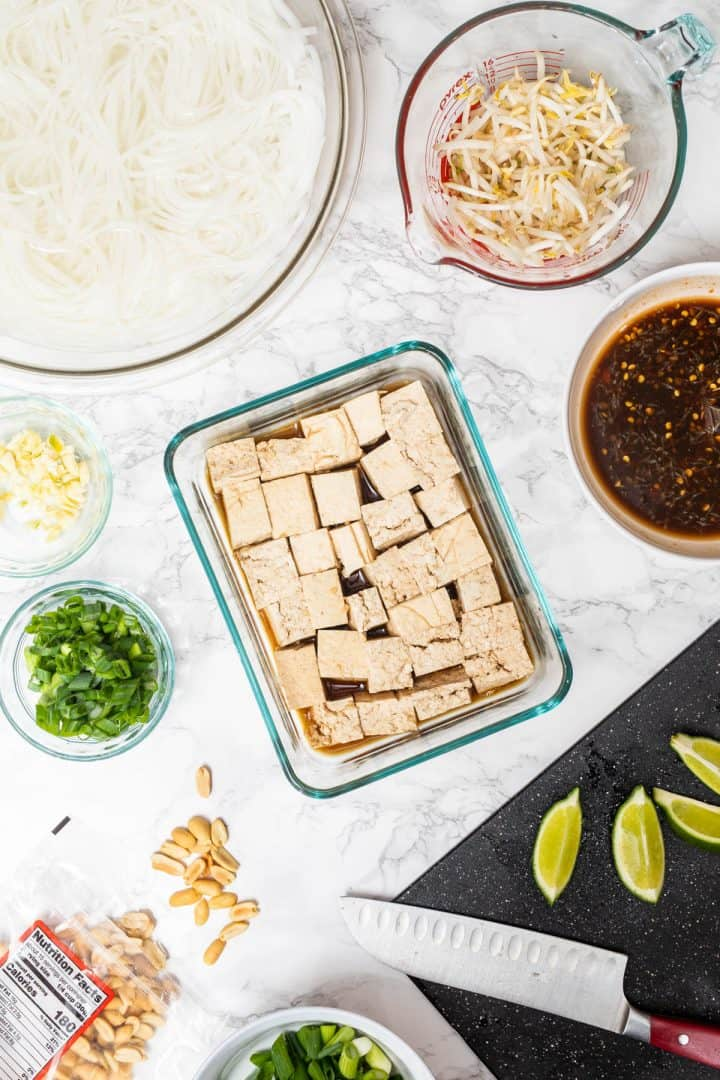 Overhead photo of marinating tofu cubes surrounded by pad thai ingredients, uncooked noodles, and sauce