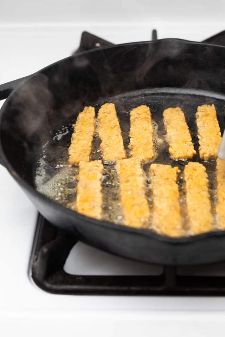 Tempeh bacon cooking in cast iron pan