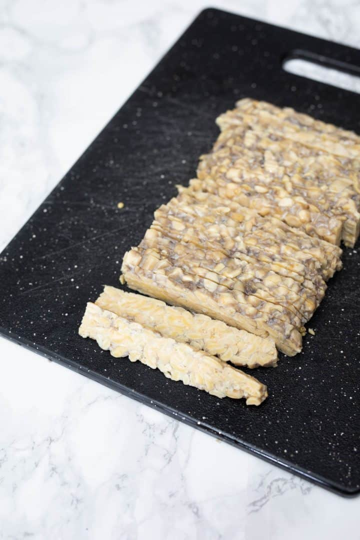 Sliced uncooked tempeh on cutting board