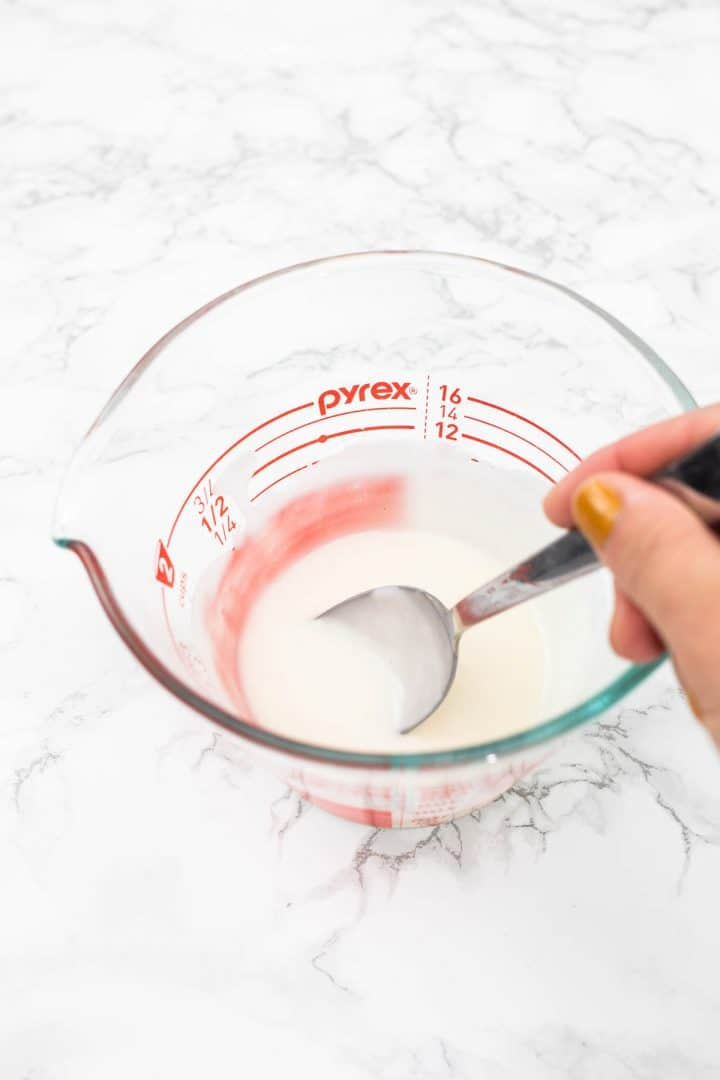 Hand stirring icing in glass measuring cup