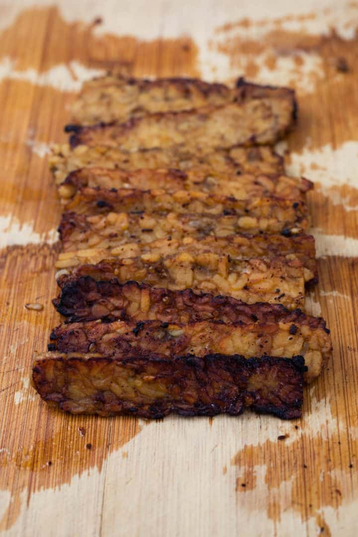 Cooked tempeh bacon on wooden cutting board