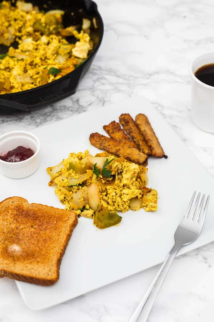 Plate of tofu scramble with tempeh bacon and toast with cup of coffee