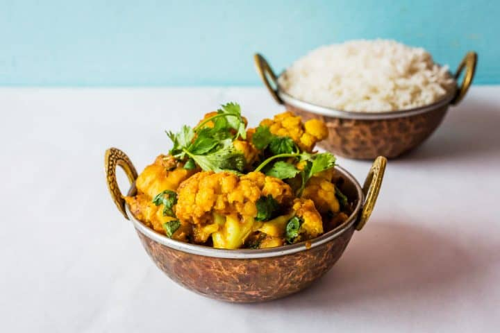 Bowl of aloo gobi in metal bowl with rice