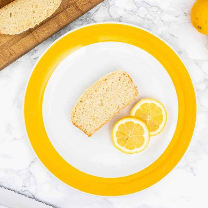 Slice of lemon loaf on yellow and white plate