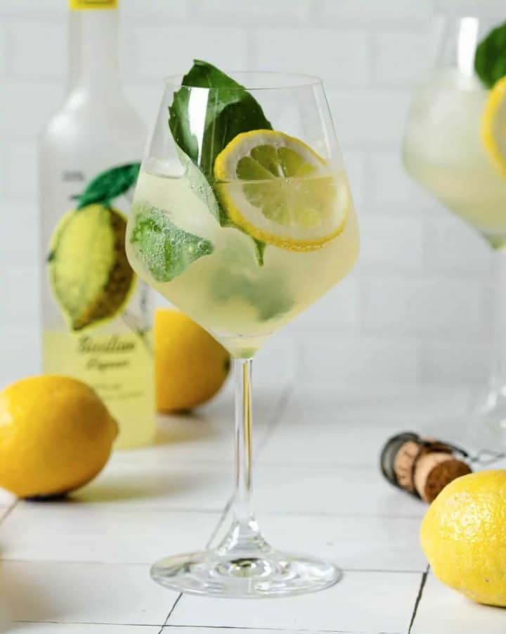 Limoncello drink in wine glass with basil and lemon slices