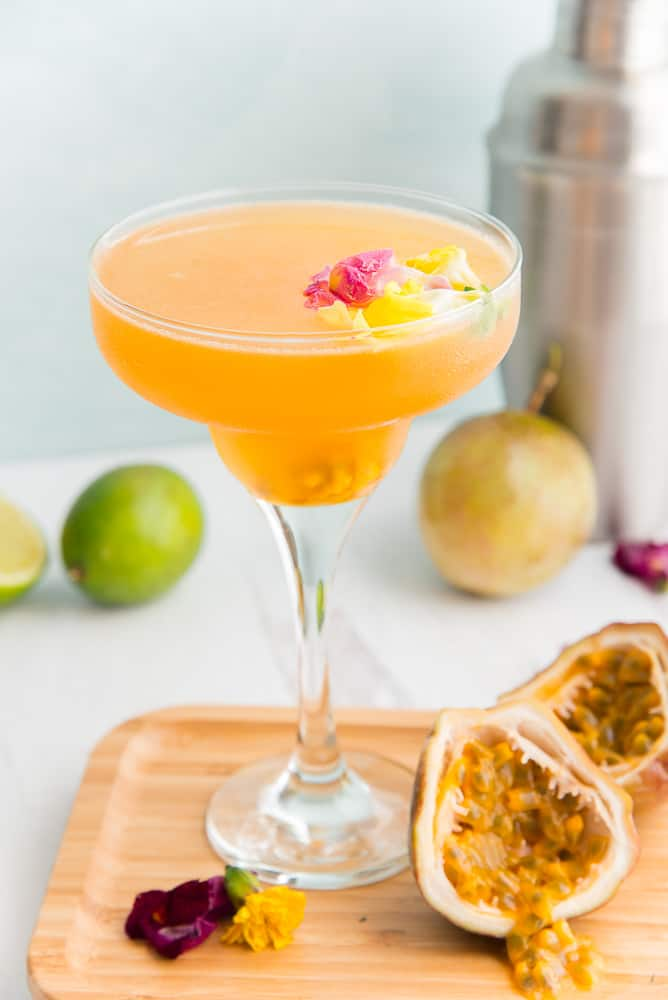 Passionfruit cocktail on cutting board with fresh passionfruit