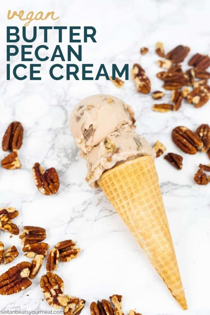 """Two scoops of ice cream in sugar cone on marble surrounded by pecans with text """"Vegan Butter Pecan Ice Cream"""""""