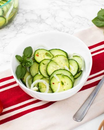 Bowl of cucumber salad on table