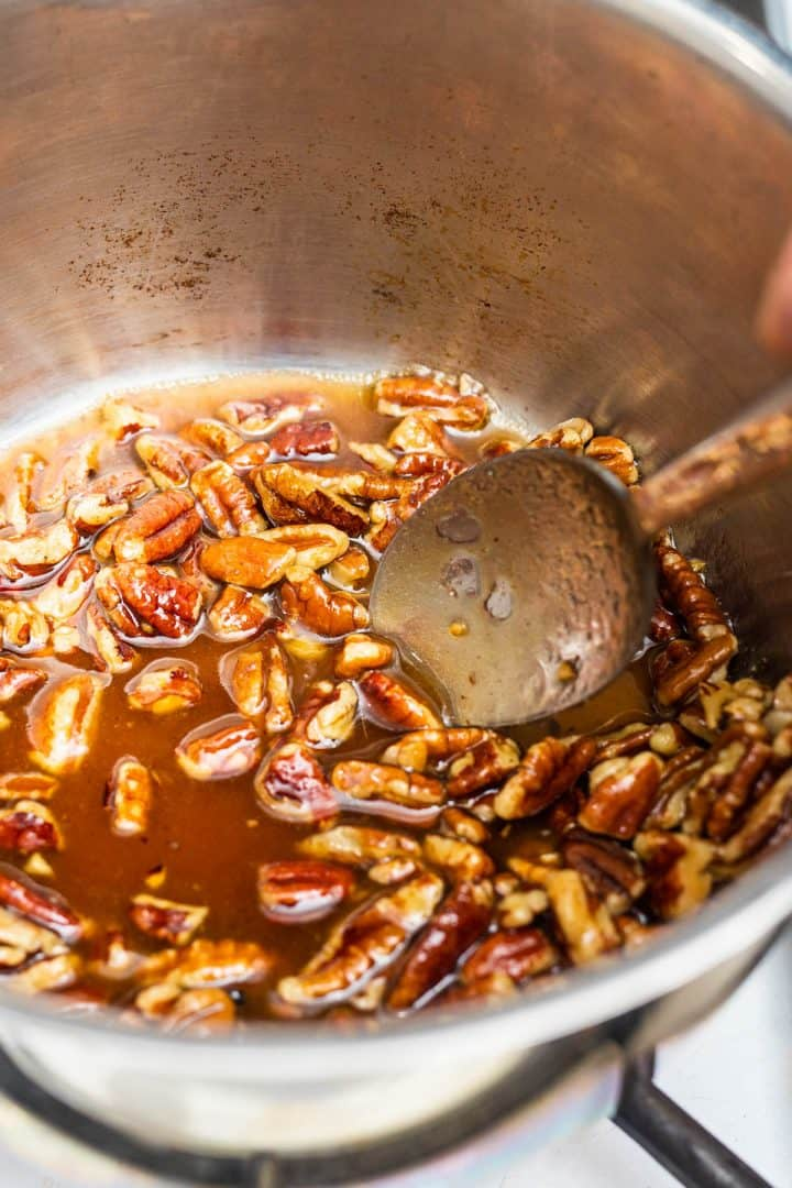 Pecans in sugar syrup in pot on stove with spoon