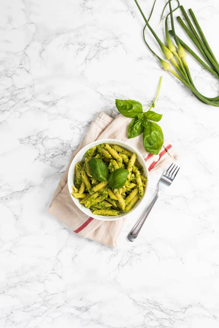 Bowl of garlic scape pesto garnished with fresh basil leaves and garlic scapes on the side