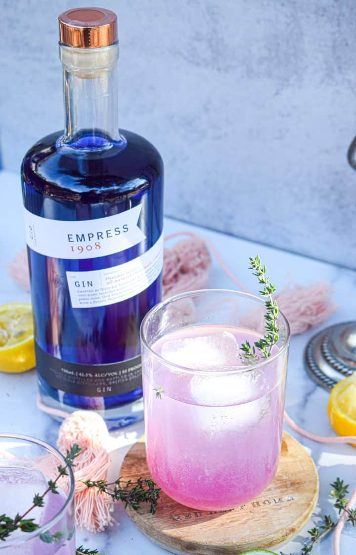 Purple gin cocktail on wooden coaster with blue bottle of Empress gin