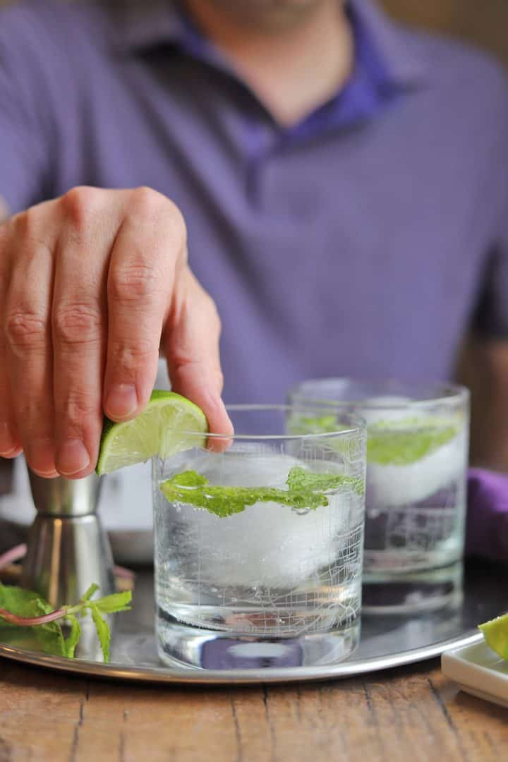Gin and tonic cocktails on tray with hand placing lime wedge on glass