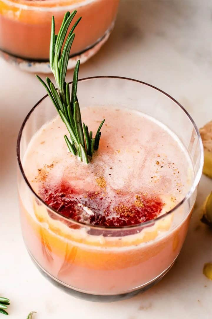 Grapefruit cocktail with grapefruit slice and rosemary sprig in glass
