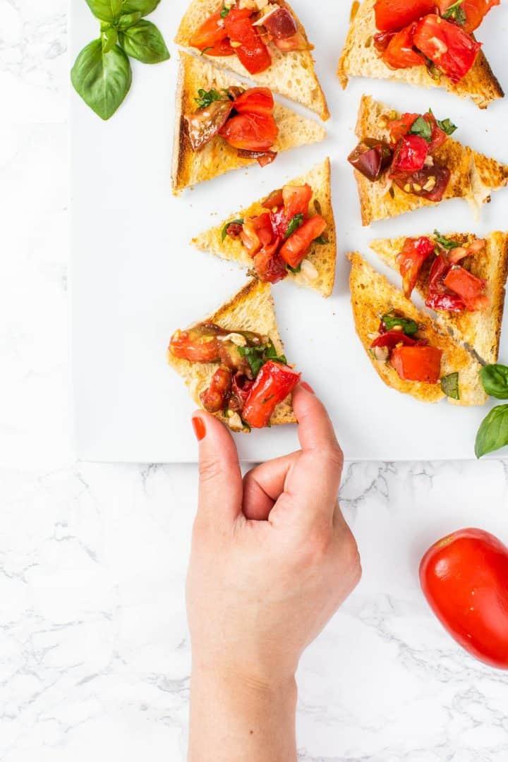 Hand reaching for piece of bruschetta on plate