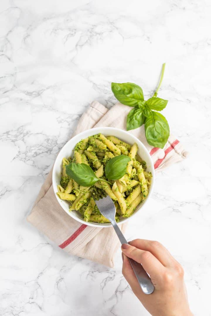 Hand with fork reaching into bowl of pesto pasta on white counter