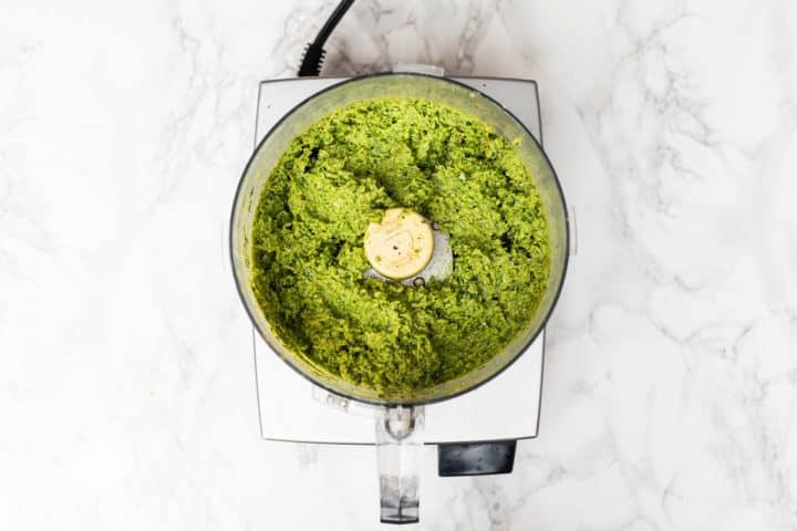 Overhead view of food processor filled with garlic scape pesto