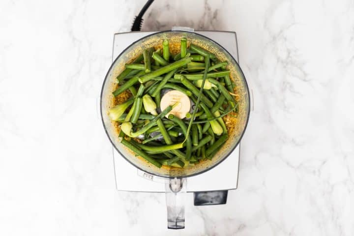 Overhead view of food processor filled with chopped garlic scapes and nuts