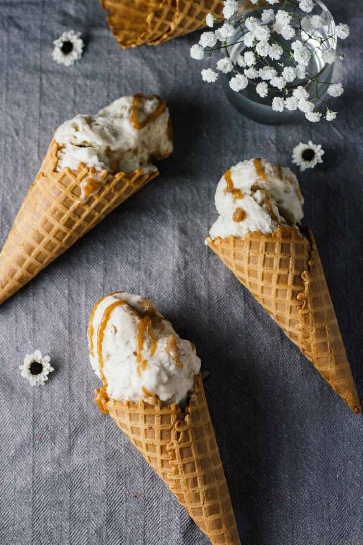 3 ice cream cones on gray tablecloth with chamomile flowers