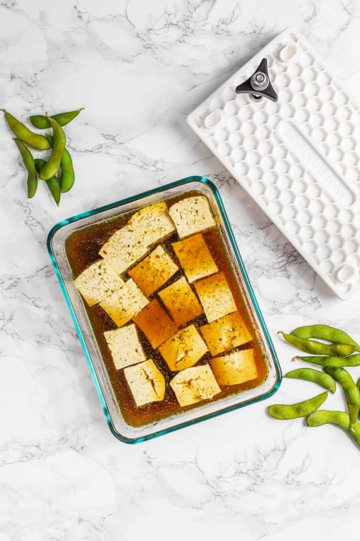 Tofu cubes marinating in a glass dish with EZ Tofu Press and edamame pods off to side