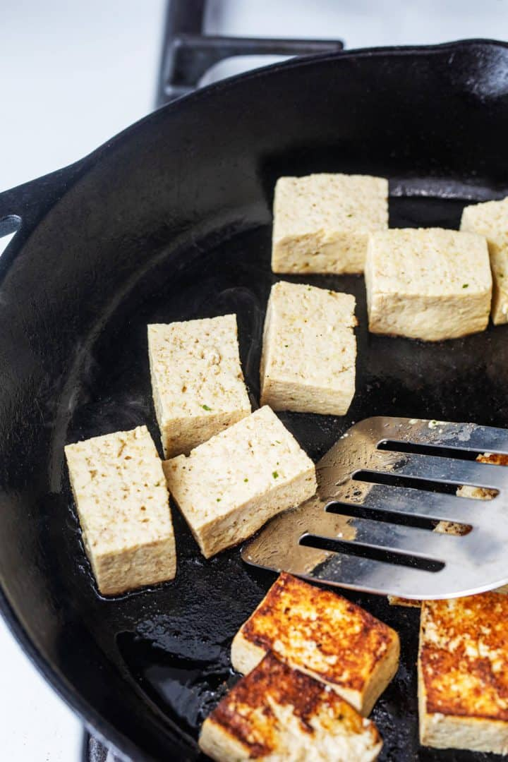 Metal spatula flipping tofu cubes in cast iron skillet
