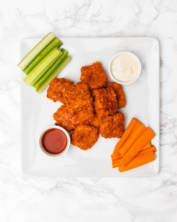 Overhead view of plate of buffalo tofu wings on plate with celery sticks, carrot sticks, ranch dressing, and buffalo sauce
