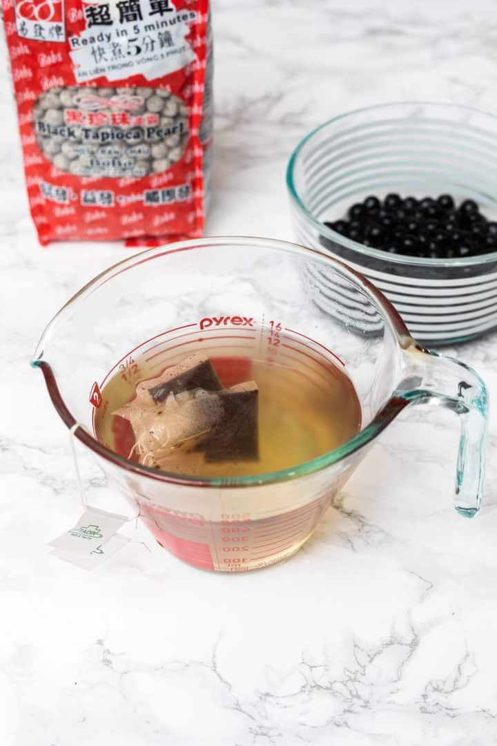 Two tea bags steeping in glass measuring cup with bag of boba and container of prepared boba off to side