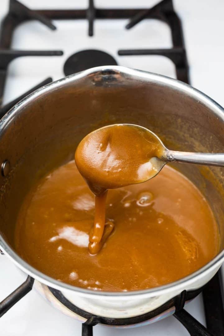 Vegan caramel sauce in saucepan dripping off metal spoon