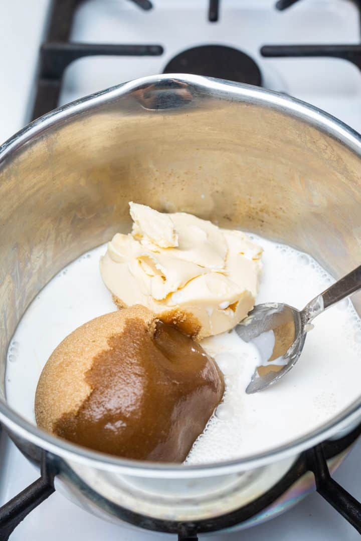 Non-dairy milk, brown sugar, and margarine in saucepan on stove with spoon