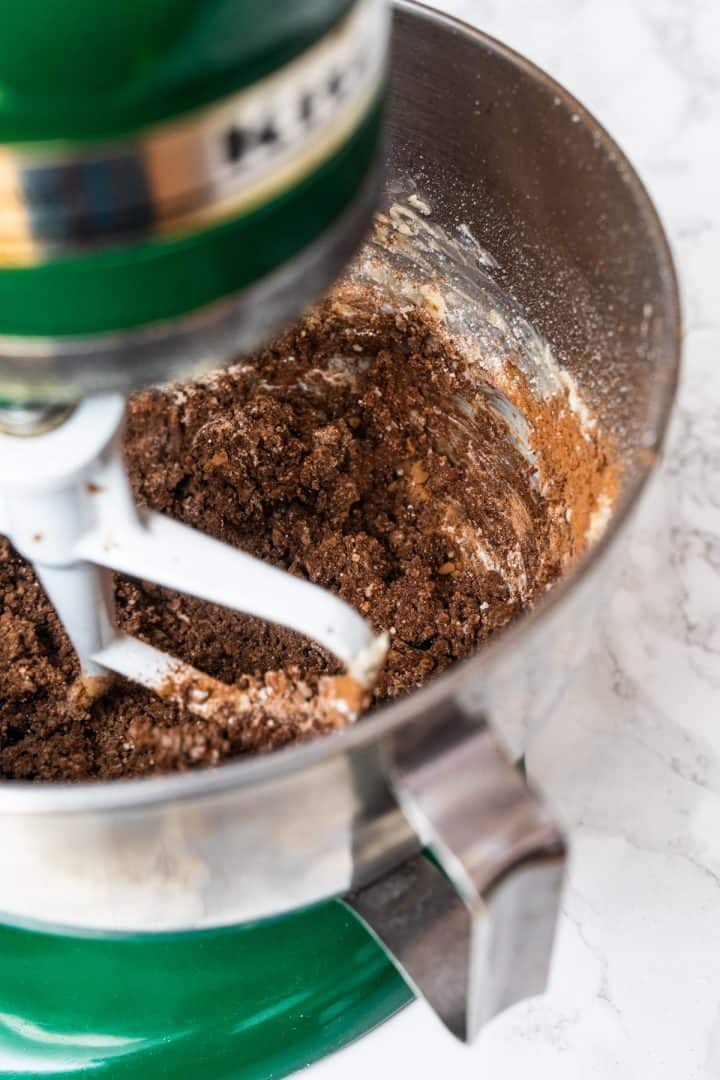 Chocolate frosting ingredients mixing up in stand mixer on counter