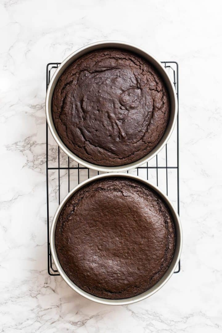 Two baked chocolate cakes on cooling rack shot from overhead