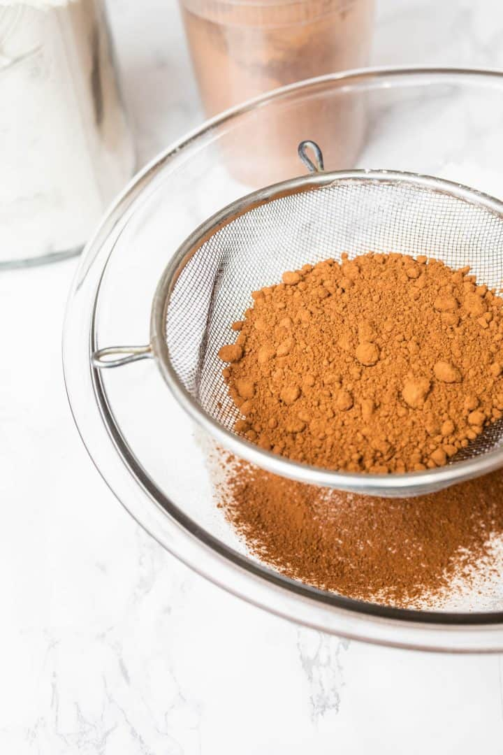 Cocoa powder being sifted into large glass bowl full of sifted flour