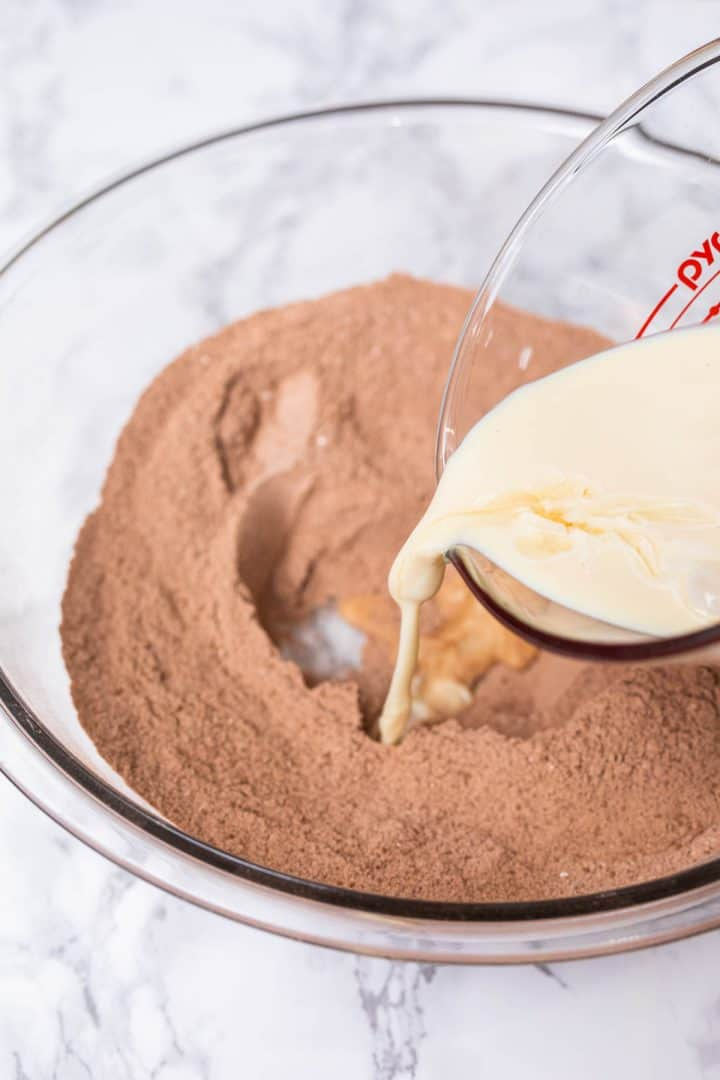 Non-dairy milk being poured into well in dry ingredients for chocolate cake