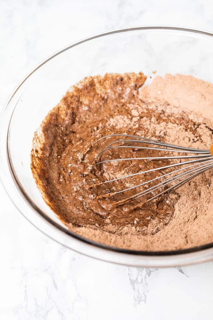 Whisk mixing dry ingredients into wet for chocolate cake batter