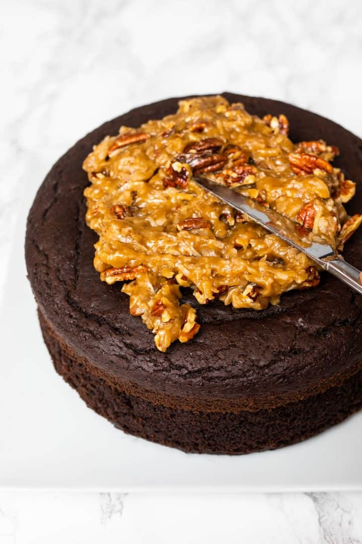 Two layers of chocolate cake with knife spreading German chocolate cake pecan coconut frosting on top