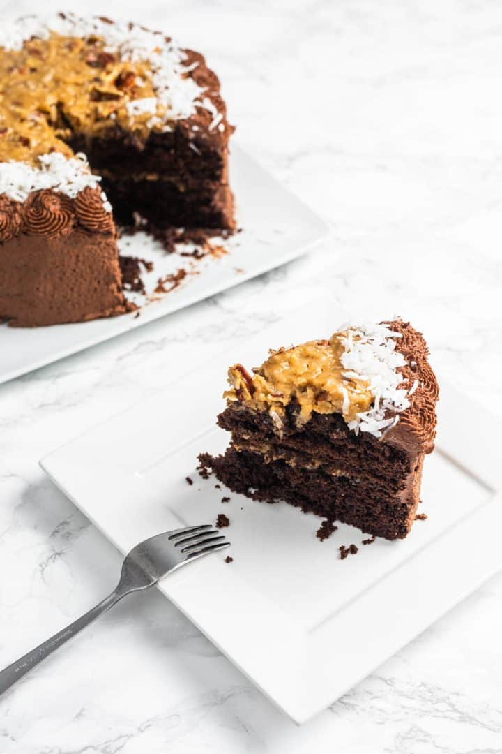 Slice of German chocolate cake on plate with remainder of cake on plate in background