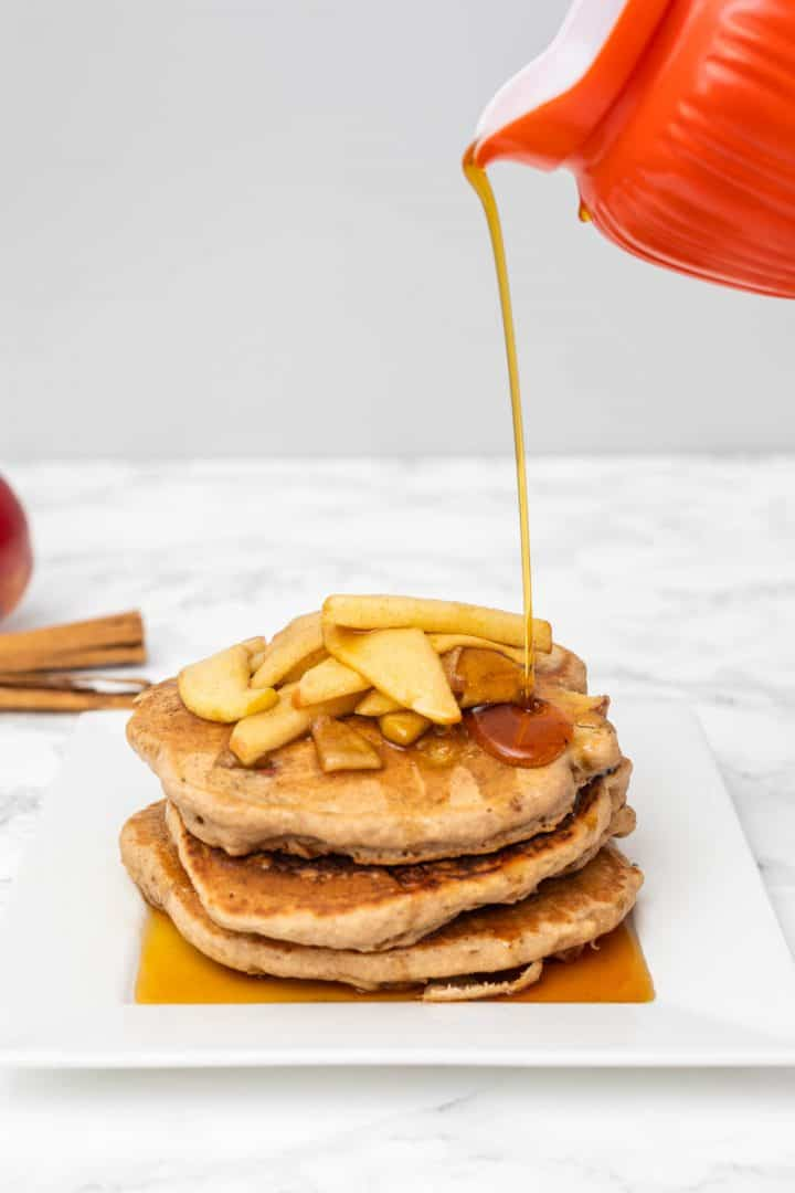Stream of syrup pouring on plate of pancakes topped with cooked apples