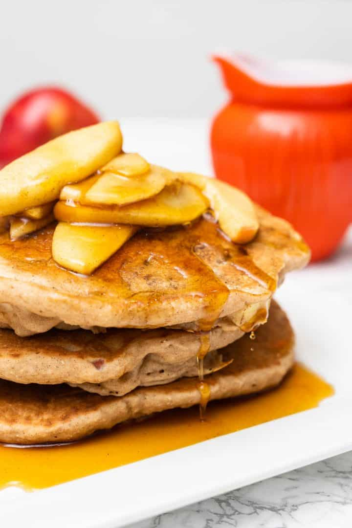 Close up of 3 apple pancakes with syrup dripping down side on plate