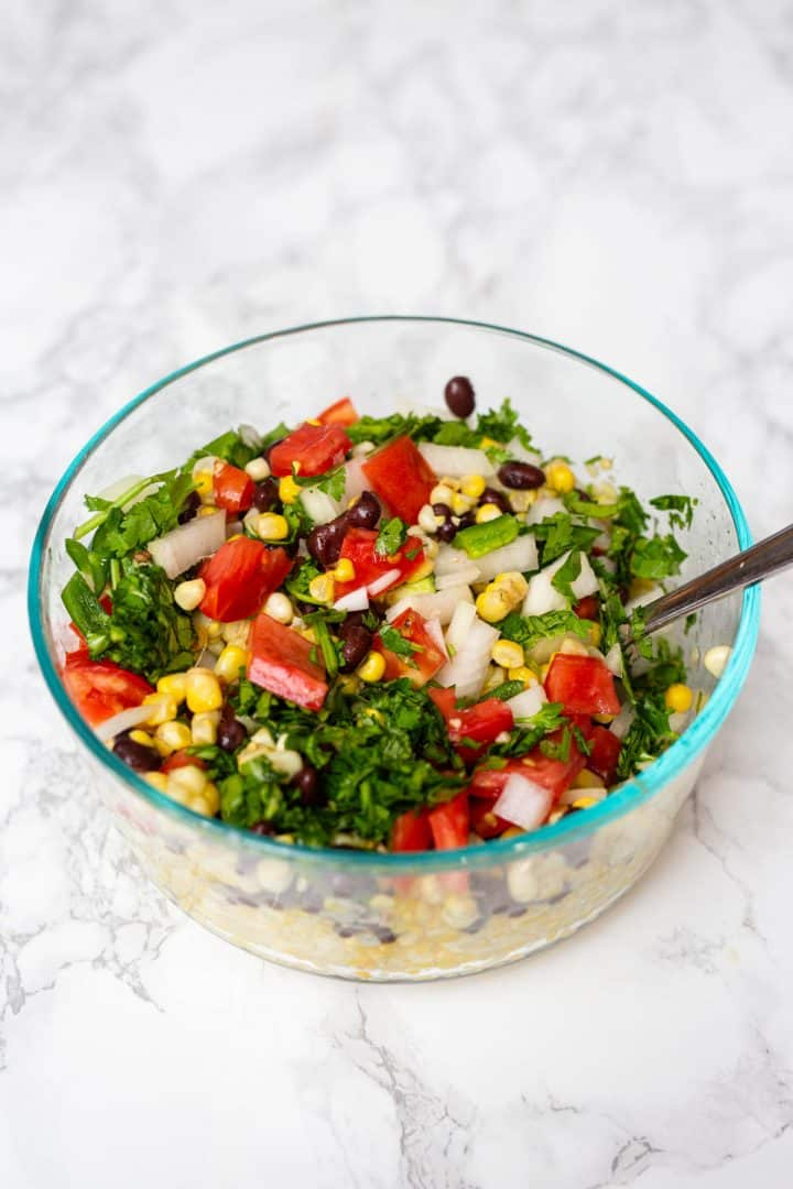 Bowl of corn with chopped fresh veggies on top to mix in