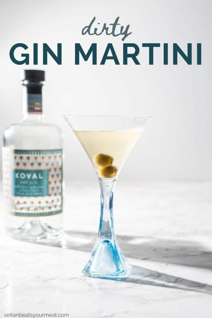 """Dirty gin martini with olives in glass with bottle of Koval gin in background with text """"Dirty Gin Martini"""""""