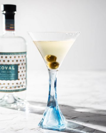 Dirty gin martini with olives in glass with bottle of Koval gin in background