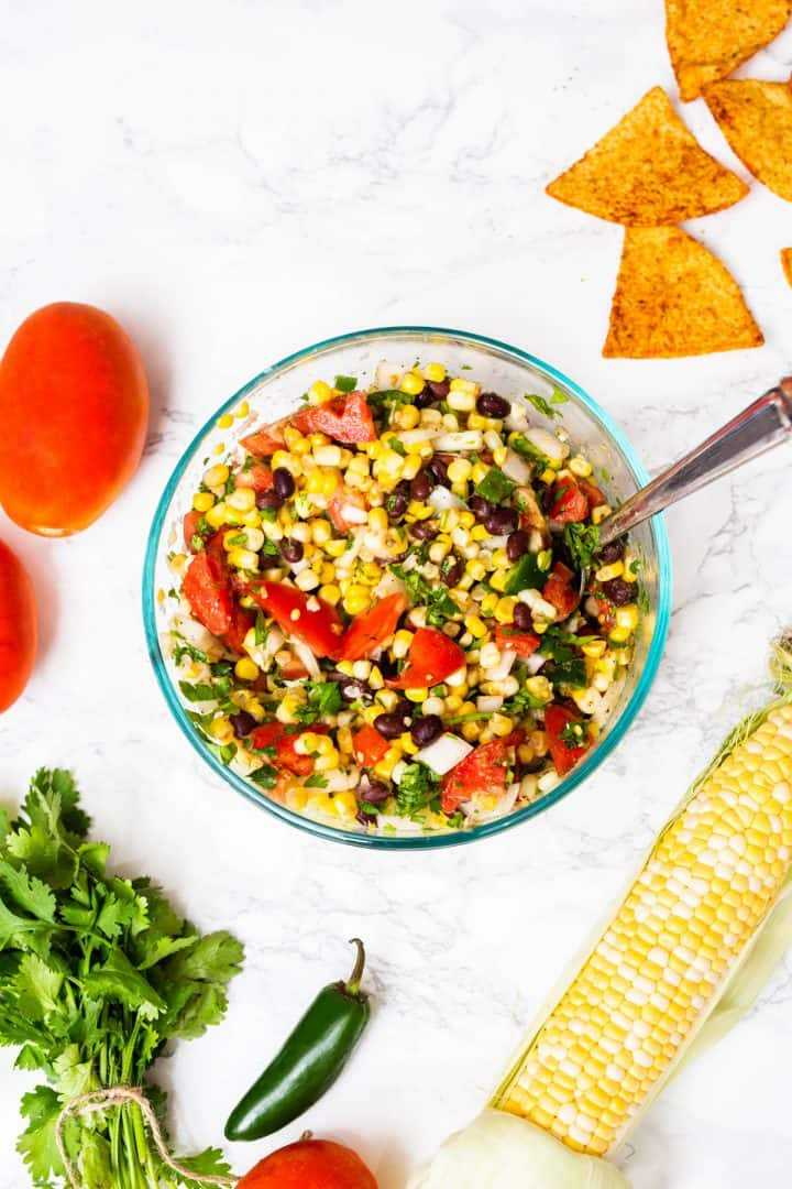 Bowl of corn and black bean salsa in glass bowl surrounded by ingredients