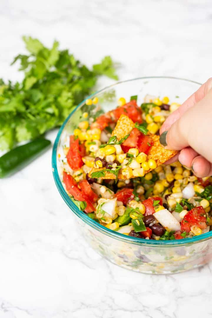 Hand dipping chip into corn salsa