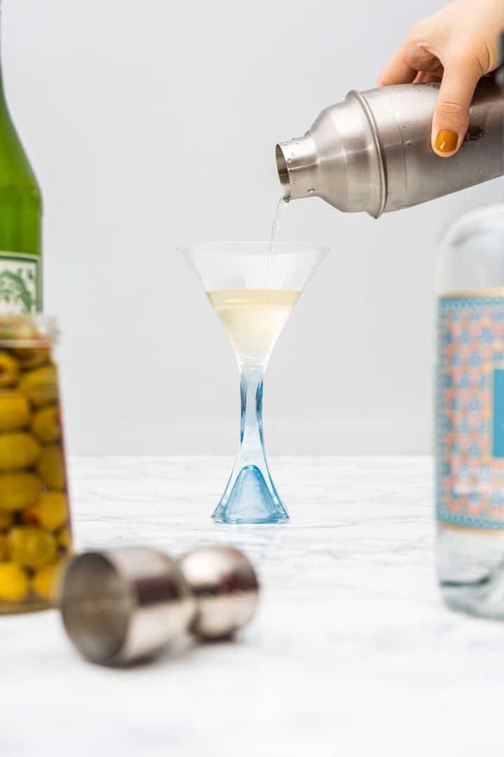 Hand pouring cocktail into martini glass from shaker surrounded by liquor bottles