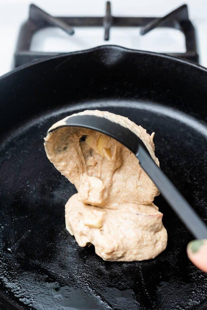Ladle of apple pancake batter pouring onto cast iron pan