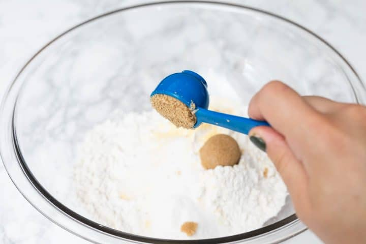 Hand pouring measuring spoon of brown sugar into mixing bowl