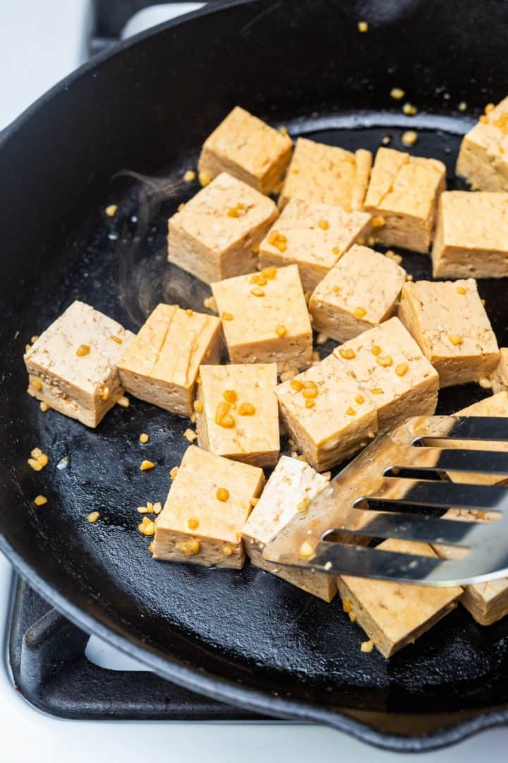 Cubed tofu with garlic pan frying in cast iron pan on stove